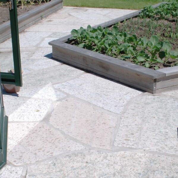 Hyvlade kalkstenshällar i trädgårdsmiljö
